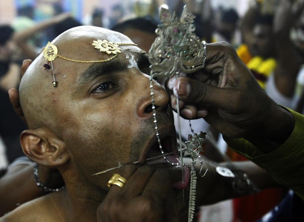 бритый индус прицепляет к себе кавади