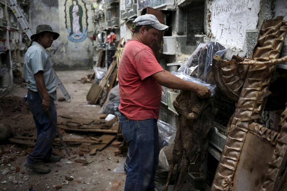 Работник кладбища упаковывает труп в пакет