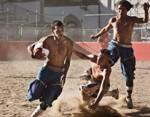 игрок пытается удержать мяч